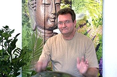 Therapeut Martin Bathe vor einem asiatischen Wandbild.